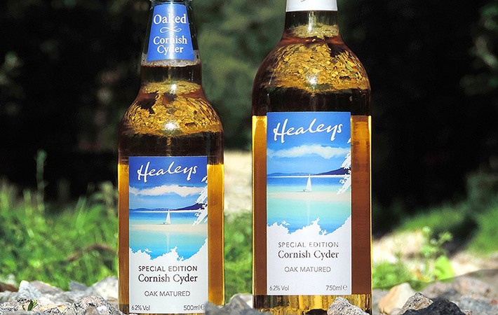 a small and a large bottle next to each other showing the label design for special edition cornish cyder