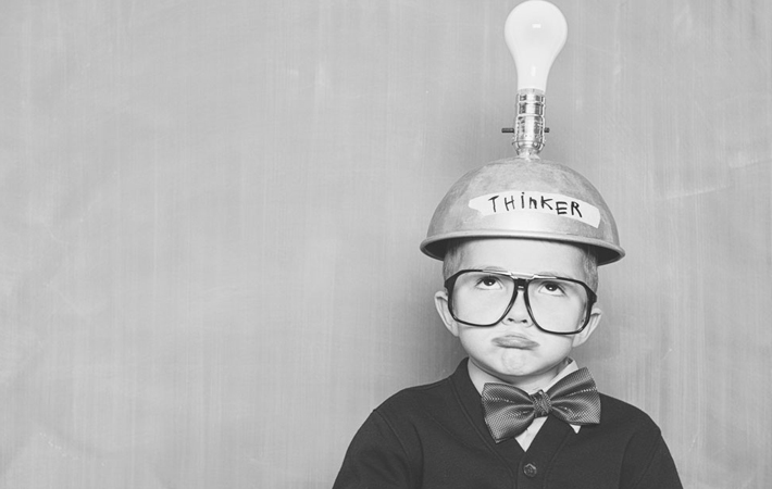 a child with a lightbulb thinker helmet on his head
