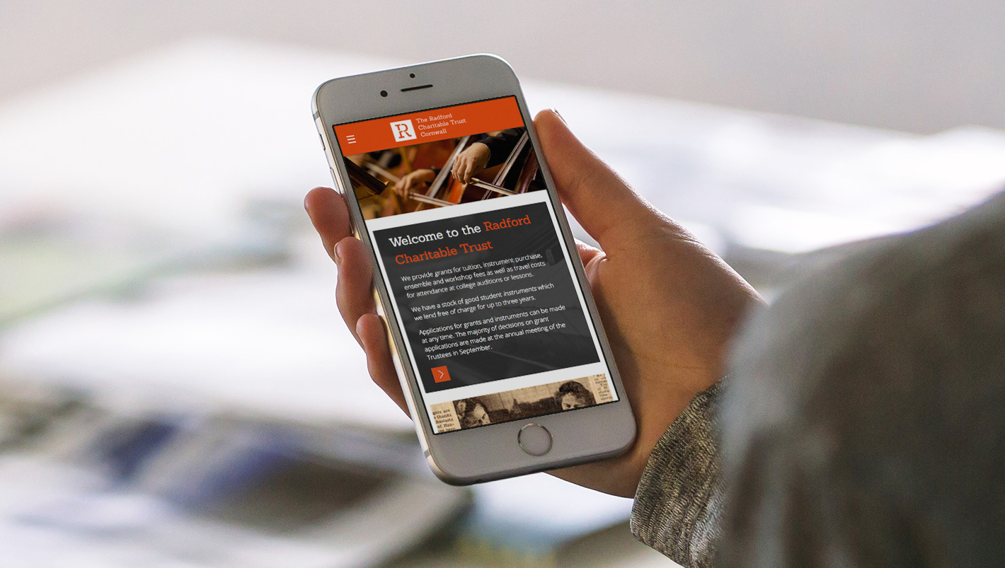 a student holding a mobile phone showing a responsive version of the radford trust website